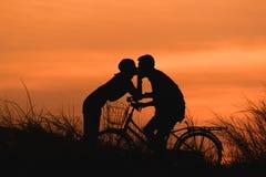 Siluetee los pares que se besan en la bici sobre fondo de la puesta del sol Imágenes de archivo libres de regalías