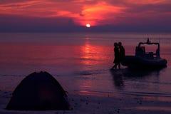 Siluetee los pares que se besan y que acampan en la playa Imagen de archivo libre de regalías