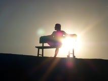 Siluetee sentarse en puesta del sol Foto de archivo libre de regalías