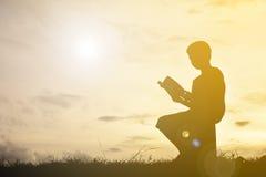 Siluetee un libro de lectura del muchacho Imagen de archivo libre de regalías