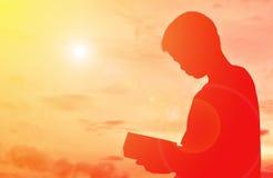 Siluetee un libro de lectura del muchacho Foto de archivo