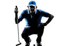 Siluetta accovacciantesi golfing del giocatore di golf dell'uomo Immagini Stock