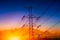 Siluetta ad alta tensione del pilone della trasmissione di elettricità con la centrale elettrica Fotografie Stock Libere da Diritti