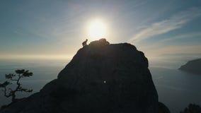 SILUETTA AEREA: la giovane donna scala una montagna Signora che raggiunge la sommit? nel bello paesaggio archivi video