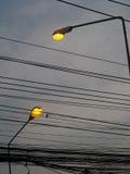 Siluetta all'aperto gialla alta della lampada di via di illuminazione di lampadina isolata con il cielo nuvoloso scuro grigio Immagini Stock Libere da Diritti