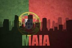 Siluetta astratta della città con la maia del testo alla bandiera d'annata del Portoghese Immagine Stock