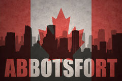 Siluetta astratta della città con testo Abbotsford alla bandiera canadese d'annata Immagine Stock