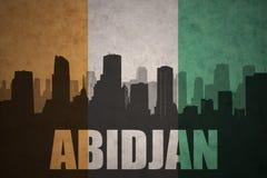 Siluetta astratta della città con testo Abidjan alla bandiera ivorian d'annata Fotografia Stock Libera da Diritti