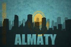 Siluetta astratta della città con testo Almaty alla bandiera d'annata del Kazakistan Immagine Stock Libera da Diritti