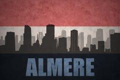 Siluetta astratta della città con testo Almere alla bandiera olandese d'annata Fotografia Stock