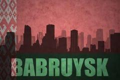 Siluetta astratta della città con testo Bobrujsk alla bandiera d'annata della Bielorussia Immagine Stock