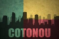 Siluetta astratta della città con testo Cotonou alla bandiera d'annata del Benin Fotografia Stock
