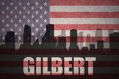 Siluetta astratta della città con testo Gilbert alla bandiera americana d'annata Fotografia Stock Libera da Diritti