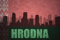 Siluetta astratta della città con testo Hrodna alla bandiera d'annata della Bielorussia Fotografie Stock