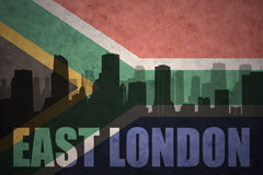 Siluetta astratta della città con testo Londra orientale alla bandiera d'annata della Sudafrica Fotografia Stock