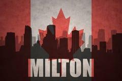 Siluetta astratta della città con testo Milton alla bandiera canadese d'annata fotografia stock