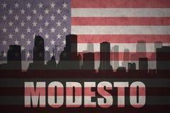 Siluetta astratta della città con testo Modesto alla bandiera americana d'annata Immagine Stock