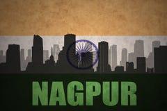 Siluetta astratta della città con testo Nagpur alla bandiera indiana d'annata Fotografia Stock