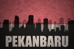 Siluetta astratta della città con testo Pekanbaru alla bandiera indonesiana d'annata Immagine Stock