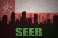 Siluetta astratta della città con testo Seeb alla bandiera d'annata dell'Oman Immagini Stock