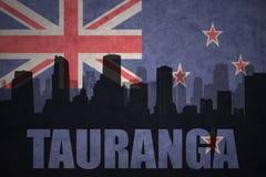 Siluetta astratta della città con testo Tauranga alla bandiera d'annata della Nuova Zelanda Immagini Stock Libere da Diritti