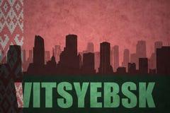 Siluetta astratta della città con testo Vitsyebsk alla bandiera d'annata della Bielorussia Fotografia Stock