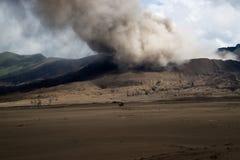 Siluetta a cavallo della guida del cavaliere attraverso il paesaggio marrone vulcanico della sabbia con fumo al supporto vicino B Immagine Stock Libera da Diritti