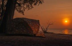 Siluetta che si accampa sulla spiaggia al tramonto Immagini Stock Libere da Diritti
