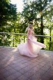 Siluetta che turbina nel tramonto nel bello legno della sposa nel vestito dalla pesca con pizzo Bionda con la a immagini stock libere da diritti