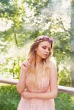 Siluetta che turbina nel tramonto nel bello legno della sposa nel vestito dalla pesca con pizzo Bionda con la a immagine stock