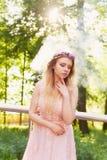 Siluetta che turbina nel tramonto nel bello legno della sposa nel vestito dalla pesca con pizzo Bionda con la a fotografia stock libera da diritti