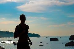Siluetta corrente della donna sulla spiaggia Immagine Stock