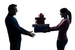 Siluetta d'offerta dei regali di natale dell'uomo della donna delle coppie Fotografie Stock