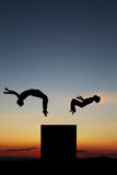 Siluetta degli adolescenti che fanno non sincronizzata nel tramonto Fotografie Stock