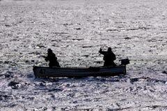 Siluetta degli uomini che pescano da una piccola barca Immagine Stock Libera da Diritti