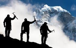 Siluetta degli uomini con la piccozza da ghiaccio a disposizione e le montagne Fotografia Stock