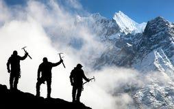 Siluetta degli uomini con la piccozza da ghiaccio a disposizione e le montagne Fotografie Stock Libere da Diritti
