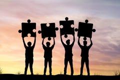 Siluetta degli uomini d'affari che tengono puzzle nel tramonto, concetto As Immagine Stock Libera da Diritti