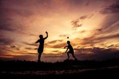 Siluetta dei bambini che giocano aeroplano di carta al tramonto immagine stock libera da diritti