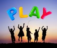 Siluetta dei bambini che giocano i palloni all'aperto Immagine Stock