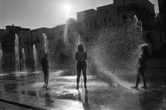 Siluetta dei bambini che giocano in una fontana immagine stock libera da diritti