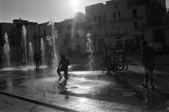 Siluetta dei bambini che giocano in una fontana fotografie stock