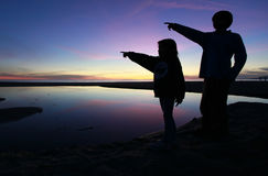 Siluetta dei bambini che indicano in un bello tramonto Fotografia Stock