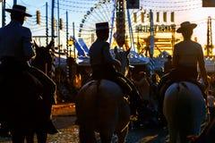 Siluetta dei cavalieri del cavallo al tramonto ` S April Fair di Siviglia Immagine Stock