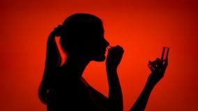 Siluetta dei cigli d'arricciatura della giovane donna Il fronte femminile del ` s nel profilo compone su fondo rosso archivi video