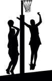 Siluetta dei giocatori del netball delle ragazze che saltano e che bloccano Fotografie Stock