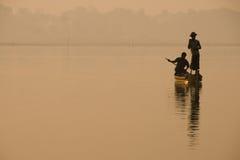 Siluetta dei pescatori alla luce dorata di mattina con un rematore del piede, sul lago Taungthaman in myanmar Fotografie Stock Libere da Diritti