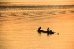 Siluetta dei pescatori con fondo arancio Fotografia Stock