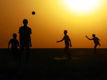Siluetta dei ragazzi che giocano a calcio all'alba Immagini Stock Libere da Diritti