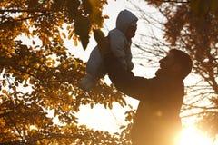 Siluetta del bambino e del papà al tramonto fotografia stock libera da diritti